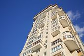 New high residential building with balconies and windows on background of blue sky.