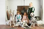 Two boys and girl in medieval costumes sit near fireplace with hanging pot with dalmatians.