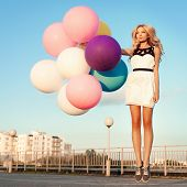 Happy Young Woman With Colorful Latex Balloons