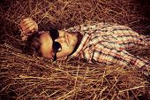 Handsome young man lying in haystack.