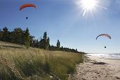 Motorized Hang Glider Kites Flying Over Secluded Beach