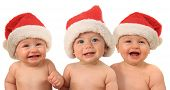 Three babies laughing babies wearing Santa hats.