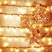 Golden Christmas baubles hanging on wooden door, decorated with glittering garland, New Year eve mag