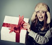Cute excited christmas girl in winter hat opening gift box, toned