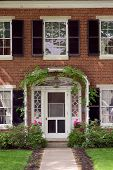 stock photo of front door  - elegant looking front door with an ivy trellis and flower pots - JPG