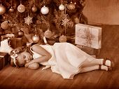 Child sleeping near Christmas tree. Black and white retro.