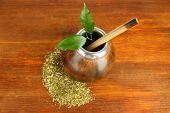 Calabash and bombilla with yerba mate on wooden background