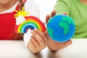 Environmental awareness and education concept - child hands holding earth globe and rainbow made of clay