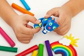 stock photo of molding clay  - Child playing with colorful clay making animal figures  - JPG
