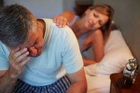 stock photo of early 50s  - Wife Comforting Husband Suffering With Insomnia - JPG