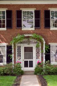 picture of front door  - elegant looking front door with an ivy trellis and flower pots - JPG
