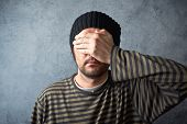 picture of blindfolded man  - Portrait of casual man covering eyes on dark gray grungy background - JPG