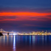 San Francisco sunset skyline and Bay Bridge in California with reflection in bay water USA