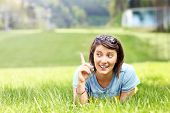 A picture of a young woman lying on the grass and pointing at something