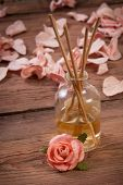 stock photo of fragrance  - Fragrance sticks or Scent diffuser with rose flowers on wooden background - JPG
