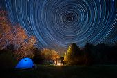 Tent Against The Night Sky With Tracks From Stars
