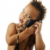 Closeup of an adorable, bare-chested preschooler pretending to talk on a plastic toy phone, though i