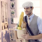 Handsome casual caucasian man holding grocery bag at vintage Paris home. Smiling, cap and french bag