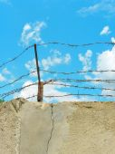 Barbed wire. Foto of wall and sky.