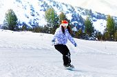 Girl in ski mask sliding with snowboard