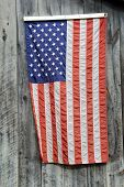Hanging flag on weathered barn boards