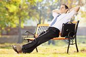 Young businessperson sitting on a bench and relaxing in a park