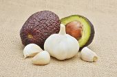 Avocado and garlic on wood background