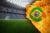 Composite image of fire surrounding brasil flag football against vast football stadium with fans in