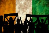 Silhouettes of football supporters against ivory coast flag in grunge effect