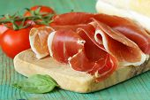 parma ham (jamon) sliced on a wooden board