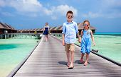 Cute little kids walking together on wooden jetty at tropical resort