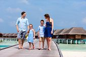 Happy beautiful family walking on wooden jetty during summer vacation at luxury resort
