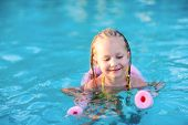 picture of noodles  - Adorable little girl swimming with a pink foam noodle in a pool while on summer vacation - JPG