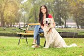 Young girl sitting on a bench in a park with her dog