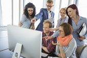 Group of smiling businesspeople using computer together in office