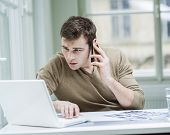 Young businessman using laptop while on call
