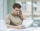 Young businessman looking at documents while using mobile phone in office
