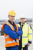 Portrait of confident worker standing with coworker in shipping yard