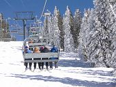 Skiers Ride The Chairlift