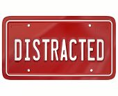 Distracted word on a red license plate to illustrate a dangerous driver who is texting or doing something diverting attention from driving on the road