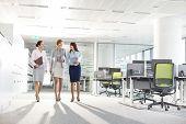 Full-length of businesswomen with file folders walking in office