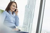 Smiling businesswoman talking on cell phone in office