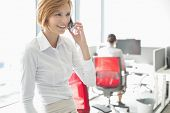 Young businesswoman talking on cell phone with colleagues in background at office