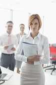 Portrait of confident businesswoman holding book with colleagues in background at office