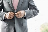 stock photo of outerwear  - Midsection of mature businessman buttoning his blazer - JPG