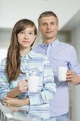 Portrait of father and daughter holding coffee cups at home