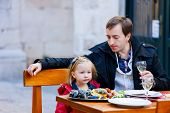 Young father and his little daughter at outdoor restaurant on autumn day