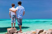Back view of father and son enjoying views of turquoise ocean water during summer vacation