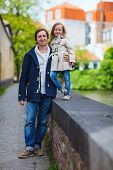 Father and his little daughter outdoors in city on a spring day