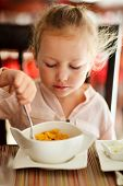 Adorable little girl eating cereal with a milk for a breakfast in restaurant
